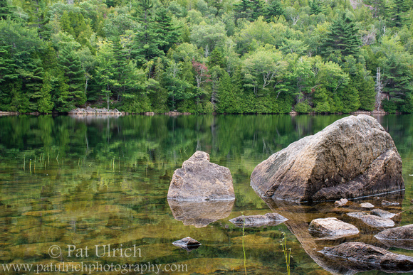 Photograph of boulders and forests reflected in Bubble Pond, Acadia National Park