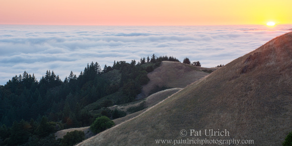 Photograph of the last rays of sunlight above the fog on Mount Tamalpais