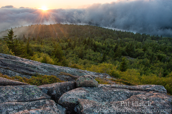 Photograph from Cadillac Mountain in Acadia National Park of the sun setting behind a fog bank